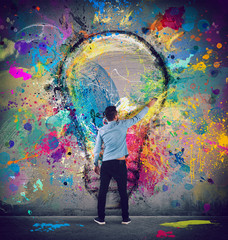 Wall Mural - Boy draws with a brush a big light bulb. Concept of innovation and creativity