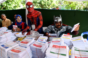 Election officials wearing superhero costumes prepare ballots at a polling station during elections in Surabaya