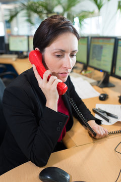 woman talking on telephone in computer control center