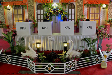 People vote at a polling center designed to look like a traditional wedding ceremony during elections in Semarang, Central Java province