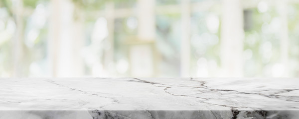 Empty white marble stone table top on blurred with bokeh shopping mall and restaurent interior banner background - can be used for display or montage your products