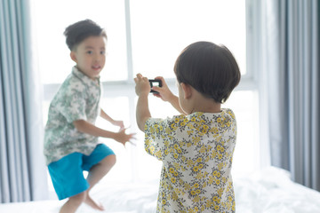 Brothers are taking a picture each other the morning on the bed.