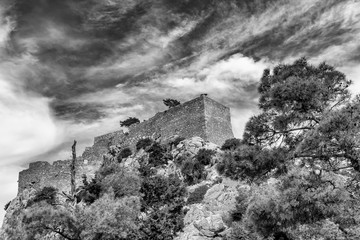 The ruins of the ancient medieval castle Monolithos against a dramatic sky, Rhodes island, Greece
