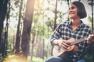 Happiness girl playing Ukulele guitar in the big forest.