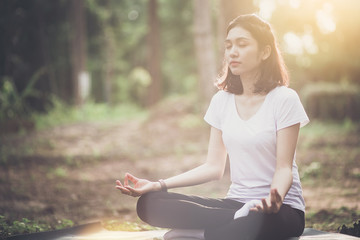 Young woman sitting and doing yoga pose with sunset and forest background.