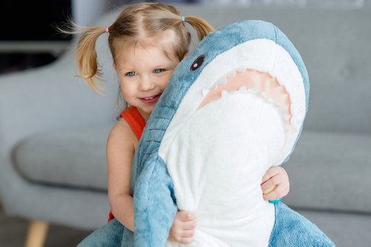 A little charming girl in a red dress is playing  with a big blue toy shark near gray sofa.