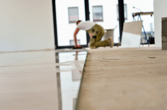Handwerker arbeitet in einem Neubau, verlegt Fliesen – selektive Schärfe, viel Copyspace