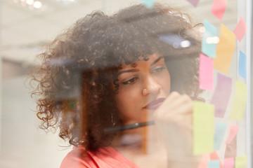 Junge Business Frau schreibt Ideen auf Haftnotizen