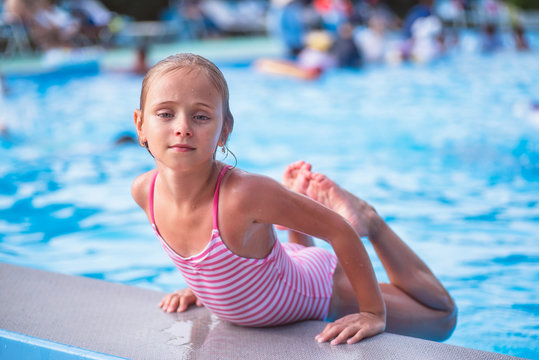 Beautiful little girl swims in the pool , cute little girl in pool in sunny day.little girl .