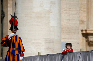 Member of the Swiss Guard stands next to a girl as Pope Francis holds his weekly audience at Saint Peter's Square at the Vatican