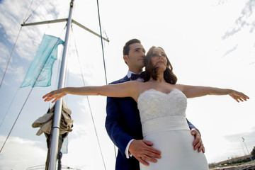 Couple of newly married lovers pose on the bow of a sailboat during their honeymoon.