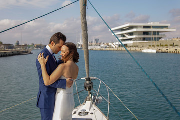 Couple of newly married lovers dance on the deck of a sailboat