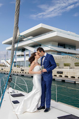 Couple of newly married lovers toasts with a glass of champagne on the deck of a sailboat.