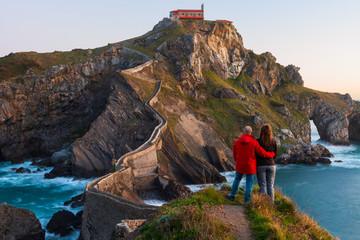 Couple against San Juan de Gaztelugatxe, its medieval stairs and bridge at sunrise, Basque Country, Spain