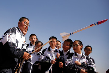 A student launches a toy rocket at the C-Space Project Mars simulation base in the Gobi Desert outside Jinchang