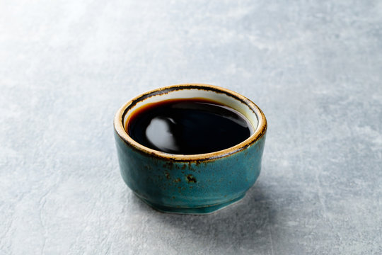 soy sauce in a plate on a gray stone background