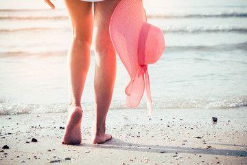 Foot of woman walking on the beach with holding pink hat