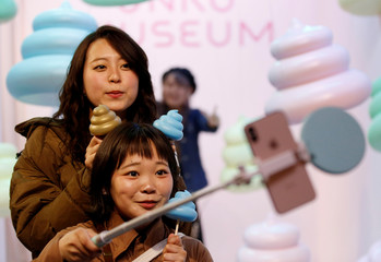 Visitors take selfies with miniature symbols of poop at the the Unko museum in Yokohama