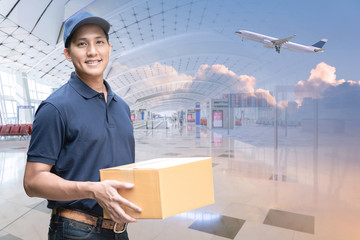 Asian delivery man holding a cardboard box with international airport background for e-commerce and logistics concept.