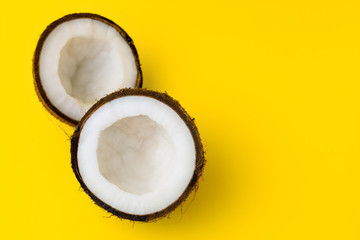 Coconut on yellow colored background, flat lay, top view