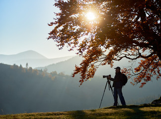 Man tourist photographer with backpack, tripod and professional camera standing under large tree with golden leaves on woody foggy mountains landscape and bright sunset in blue sky background.