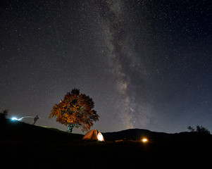 Summer camping at night. Tourist hikers tent brightly lit from inside near big tree, man silhouette and burning campfire on green grassy valley under dark blue starry sky with Milky Way constellation.