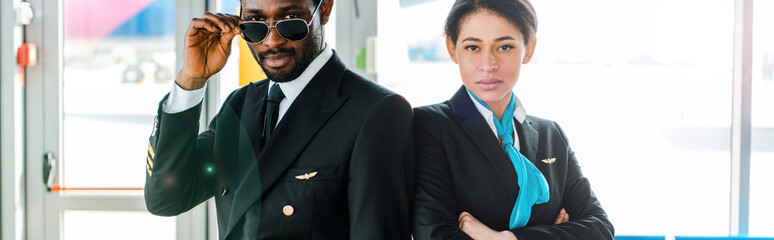 panoramic shot of african american pilot in sunglasses and stewardess with crossed arms standing together in airport Wall mural