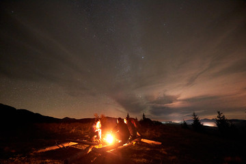 Three tourists travelers, two men and young woman sitting on big logs by burning campfire on grassy mountain valley with small spruce trees enjoying beautiful camping night under starry cloudy sky.