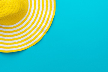 top view of yellow hat on blue background with copy space