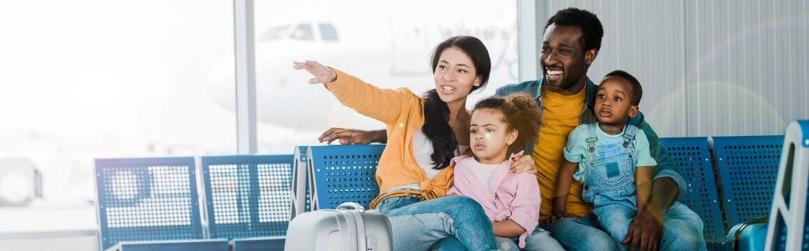 panoramic shot of smiling african american family with baggage and kids sitting in airport while mother pointing with finger away