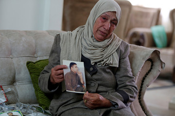 Mother of Palestinian prisoner Abdulsalam Abu Nasser, who is held in an Israeli jail, reacts as she holds his picture, in Tubas in the Israeli-occupied West Bank