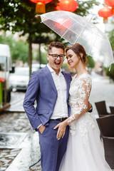 bride and groom having fun outdoors in the rain