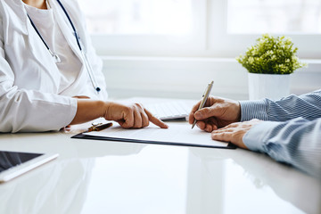 Patient signs a document with his doctor in medical office