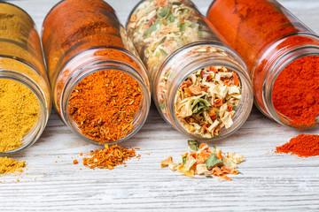 Przyprawy wysypujące się ze słoików leżących na drewnianym blacie. liofilizowane warzywa, mielona papryka, curry i mieszanki przypraw.