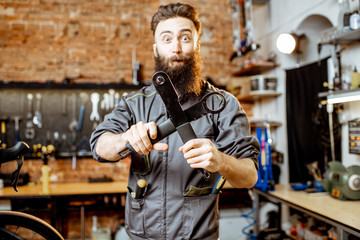 Portrait of a handsome bearded repairman in workwear standing with wrenches at the bicycle workshop