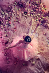 Smell of roses.Top view of beautiful young woman in pink ballet tutu surrounded by flowers. Spring mood and tenderness in coral light. Art photo. Concept of spring, blossom and nature's awakening.