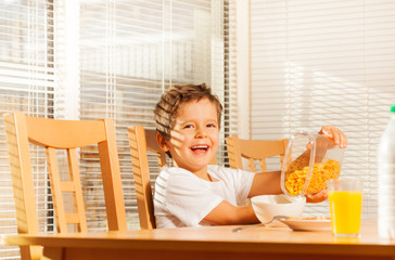 Boy pouring corn flakes making healthy breakfast