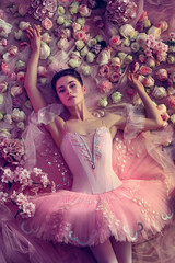Deep eyes. Top view of beautiful young woman in pink ballet tutu surrounded by flowers. Spring mood and tenderness in coral light. Art photo. Concept of spring, blossom and nature's awakening.