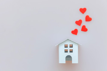 Simply minimal design with miniature white toy house and red heart isolated on white background. Mortgage property insurance dream home concept. Flat lay top view copy space