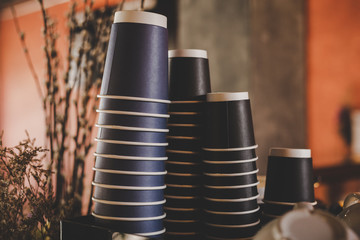 Different paper cups for coffee or tea stacked in cafe interior.