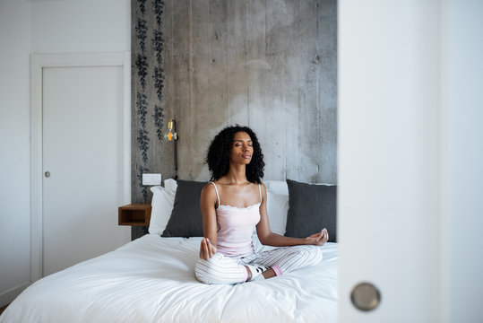 Attractive black woman on bed meditating