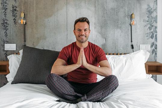 Attractive man on bed meditating