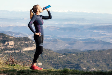 Trail runner drinking water while looking landscape from mountain peak.