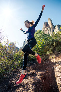Young fitness woman trail runner running and jumping on rocky mountain.