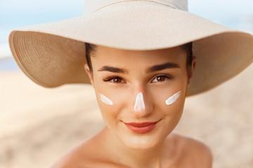 Beautiful Woman smile applying sun cream on face. Skin and  Body  care. Sun protection. Girl in bikini holding sunscreen bottle on the beach. Female in hat smear moisturizing lotion on skin