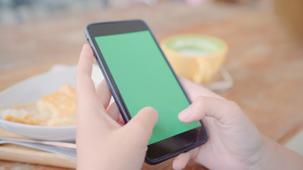 Young asian woman using black mobile phone device with green screen. Asian woman holding smartphone, scrolling pages while sitting in cafe. Chroma key.