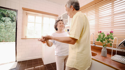 Asian elderly couple dancing together while listen to music in kitchen at home, sweet couple enjoy love moment while having fun when relaxed at home. Lifestyle senior family relax at home concept.