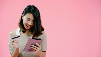 Young Asian woman using tablet buying online shopping by credit card feeling happy smiling in casual clothing over pink background studio shot. Happy smiling adorable glad woman rejoices success.