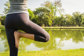 Young asian woman yoga outdoors keep calm and meditates while practicing yoga to explore the inner peace. Yoga have good benefits for health near lake at park. Sport and Healthy lifestyle concept.