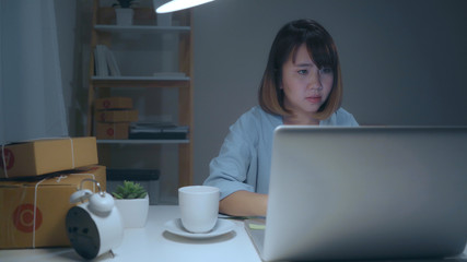 Beautiful smart Asian young entrepreneur business woman owner of SME online checking product on stock and save to computer working late in night at home. Small business owner at home office concept.